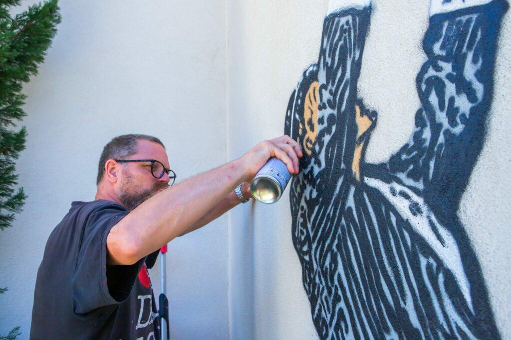 Nick Walker painting mural at 2B Art & Toys Gallery