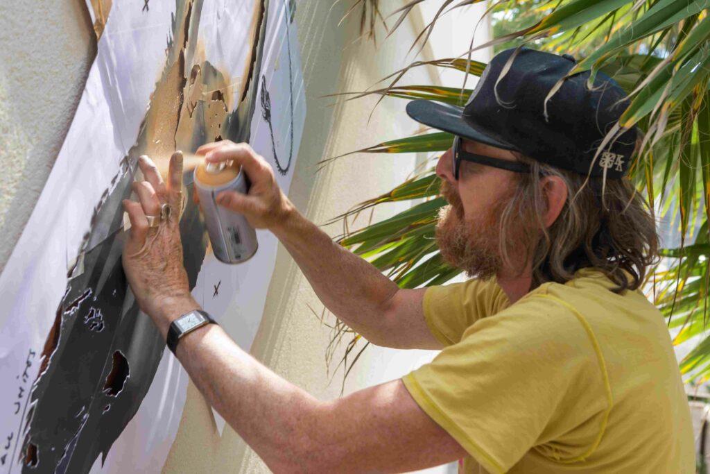 Dotmaster making mural at 2B Art & Toys Gallery