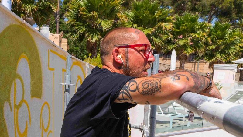 Ben Eine resting while doing a mural in Mallorca