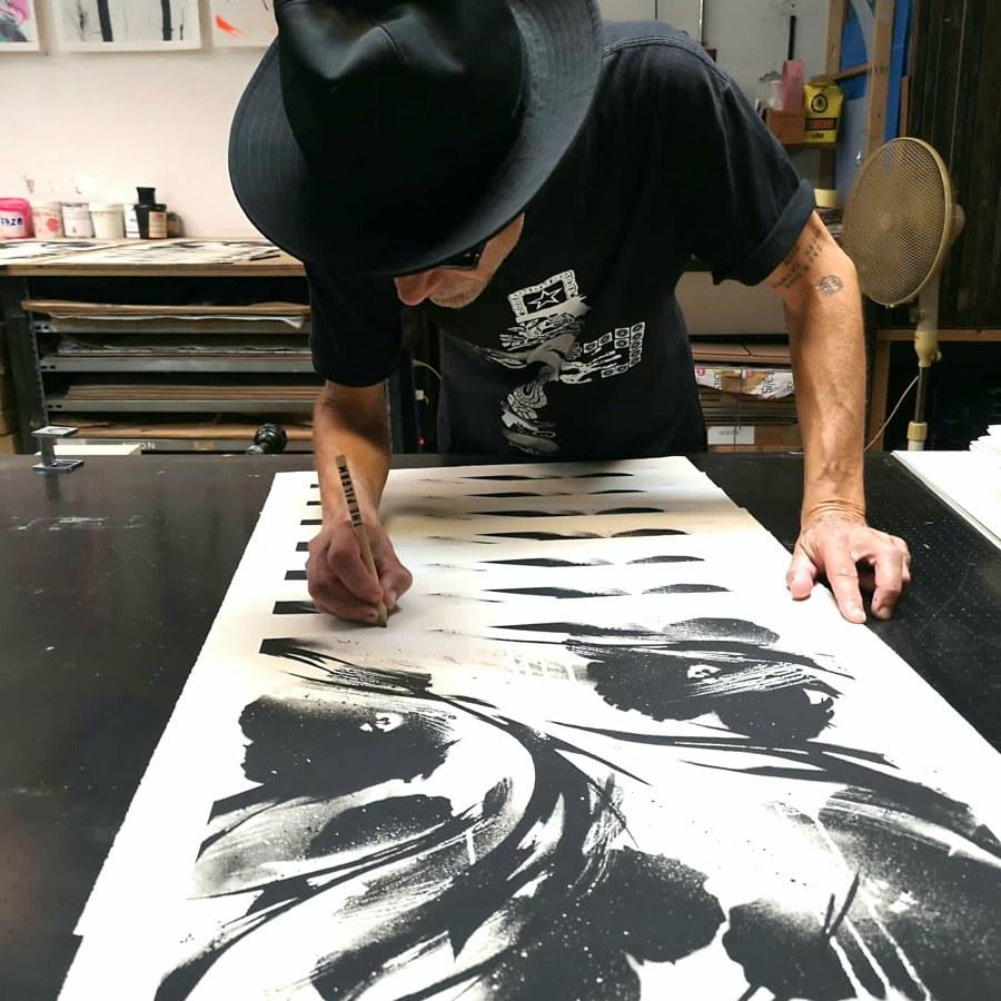 SheOne signing his BLCKFLWRS prints